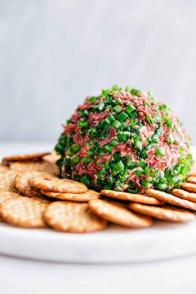 Chipped beef cheese ball on a white plate with crackers surrounding it.