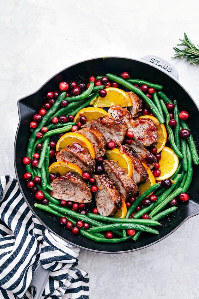 Roasted cranberry orange pork tenderloin with green beans and a black Staub skillet.