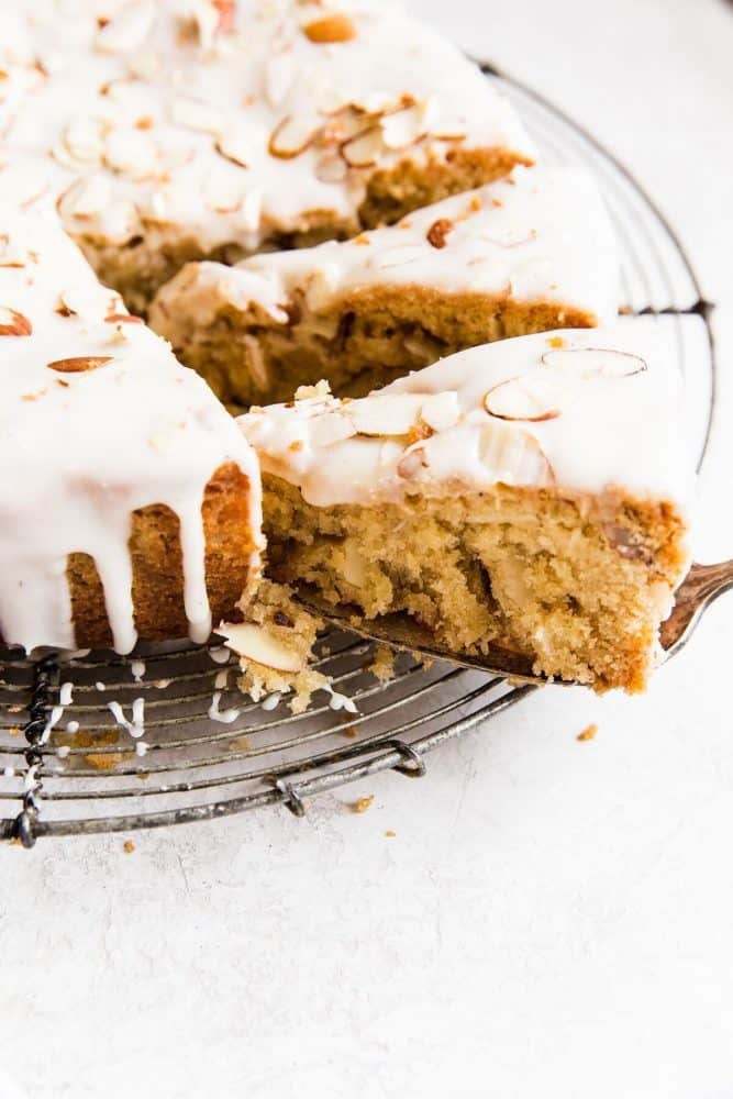 Brown butter almond cake on a cooling rack with the slice being removed.
