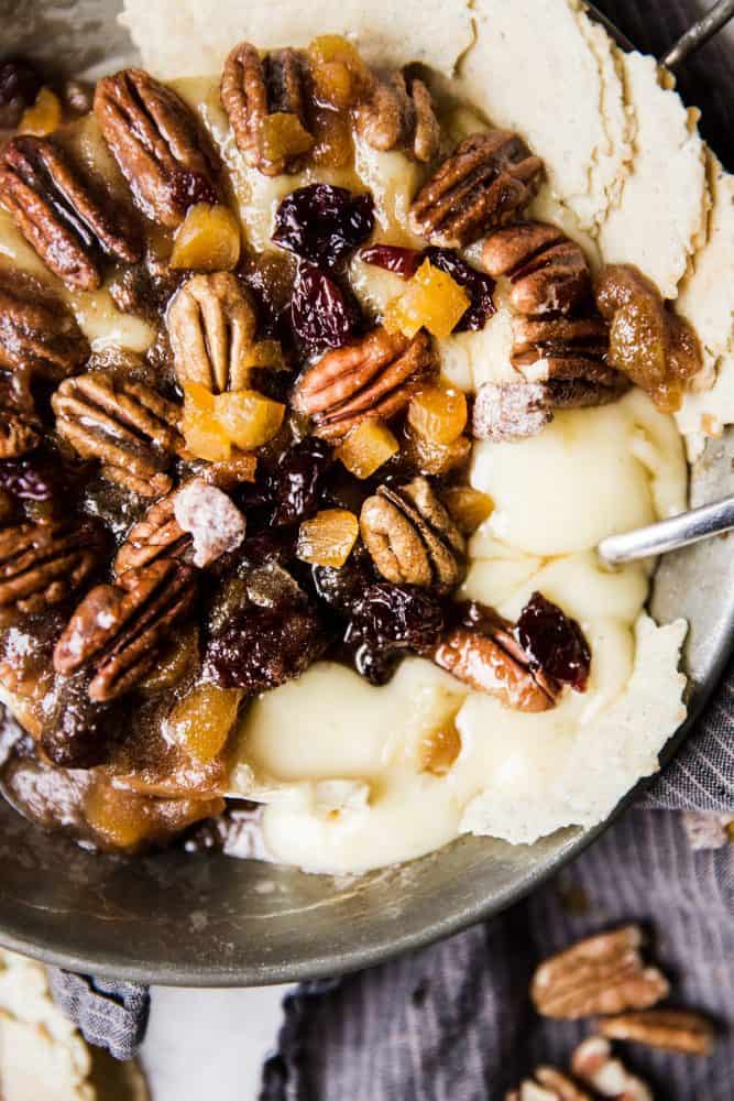 Maple pecan baked brie in a serving dish with chips on the side.