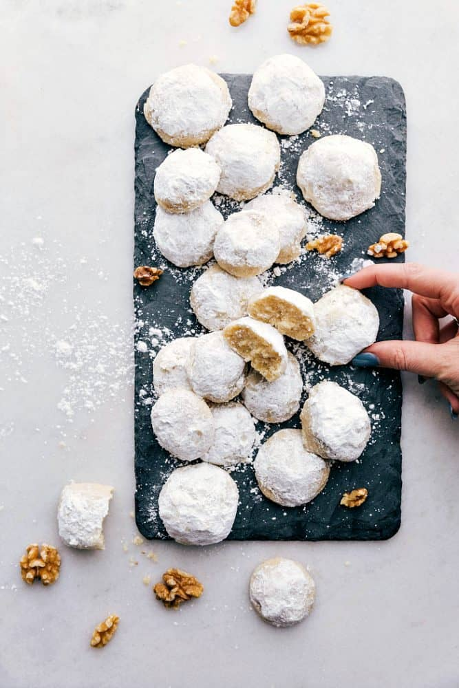Snow kiss cookies on a black cutting board.