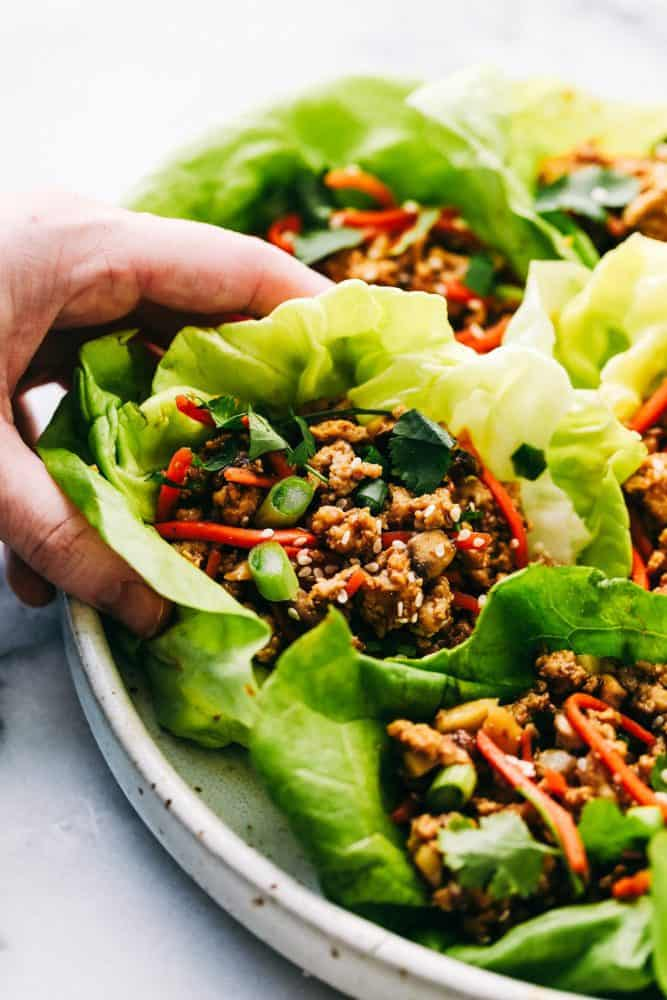 Asian lettuce wraps with a hand picking one up.