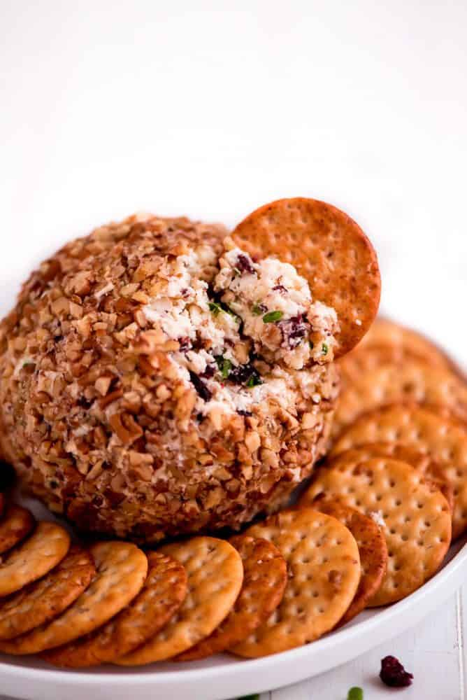 Cranberry pecan cheeseball centered in the middle of a white serving dish with crackers all around it and one crackers deck into the cranberry pecan cheese ball.