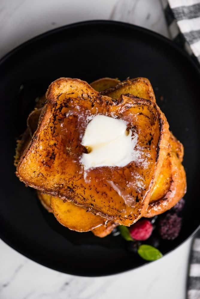 Overhead photo of crème brûlée French toast on a black plate with syrup on top.