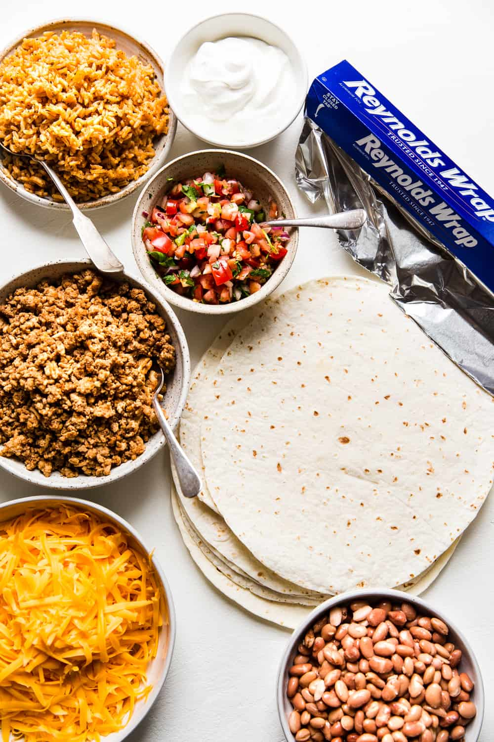 All the ingredients for a burrito. Meat, cheese, tortillas, salsa, rice, beans, aluminum foil.