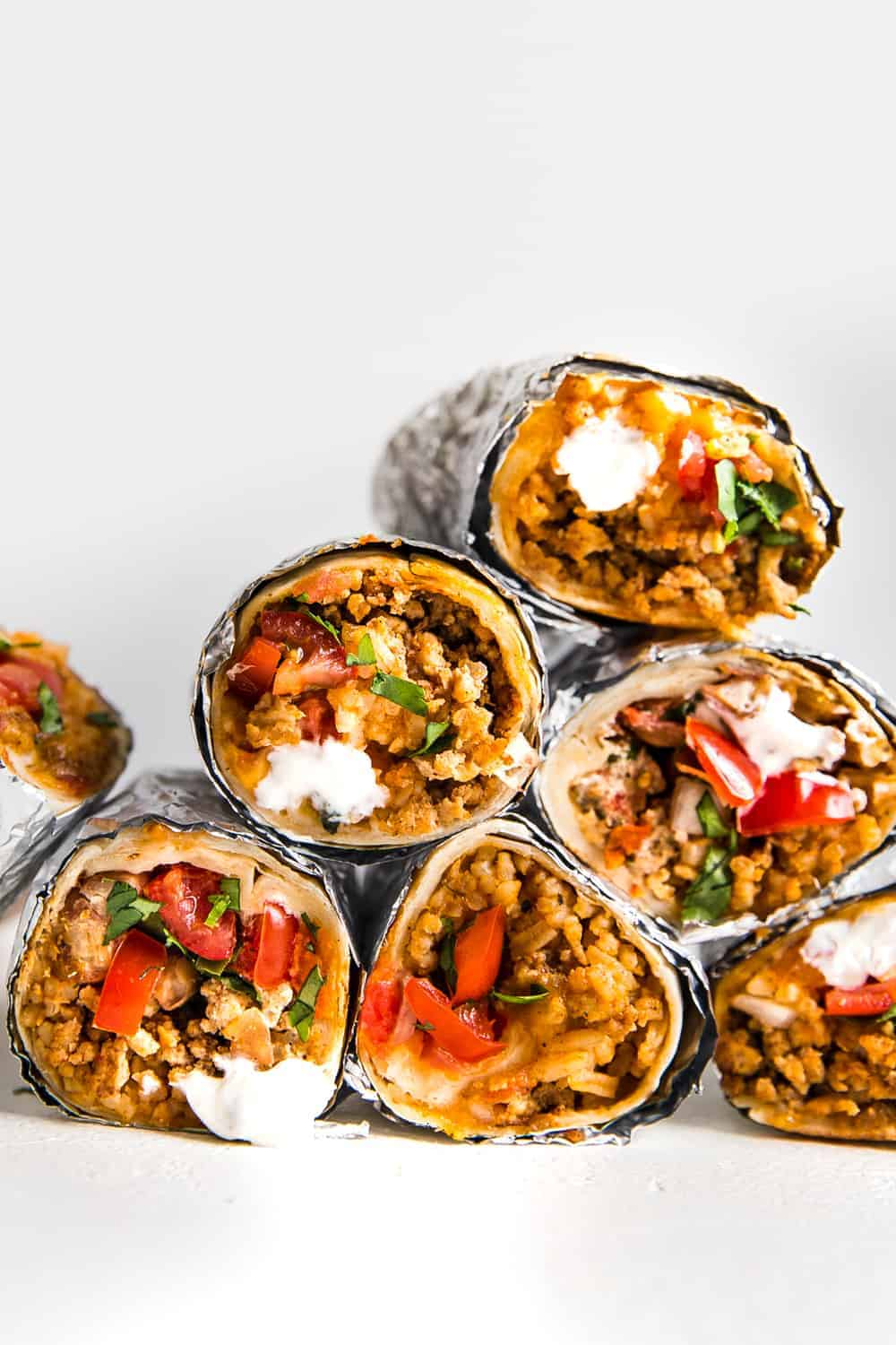 A pyramid of burritos rolled up in aluminum foil.