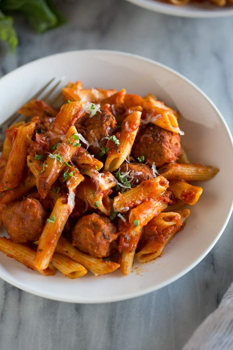 A white bowl of insta pot pasta with meatballs.