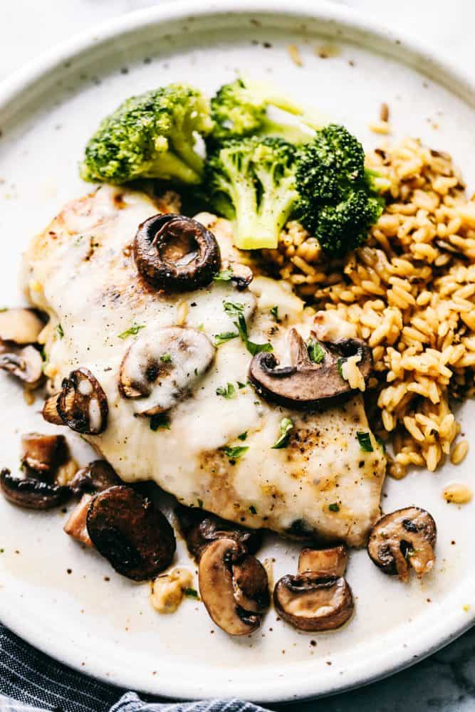Easy Baked Cheesy Mushroom Chicken on a plate with rice and broccoli.