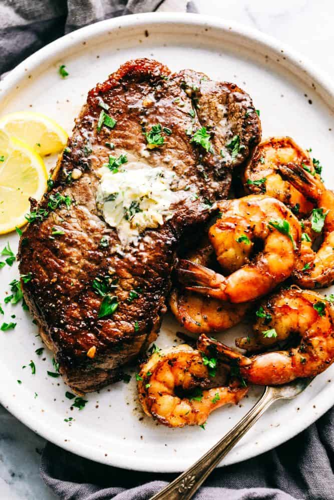 Steak and shrimp on a white plate with lemon slices on the side.