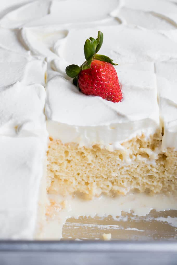 Tres leches cake with a slice already cut out.