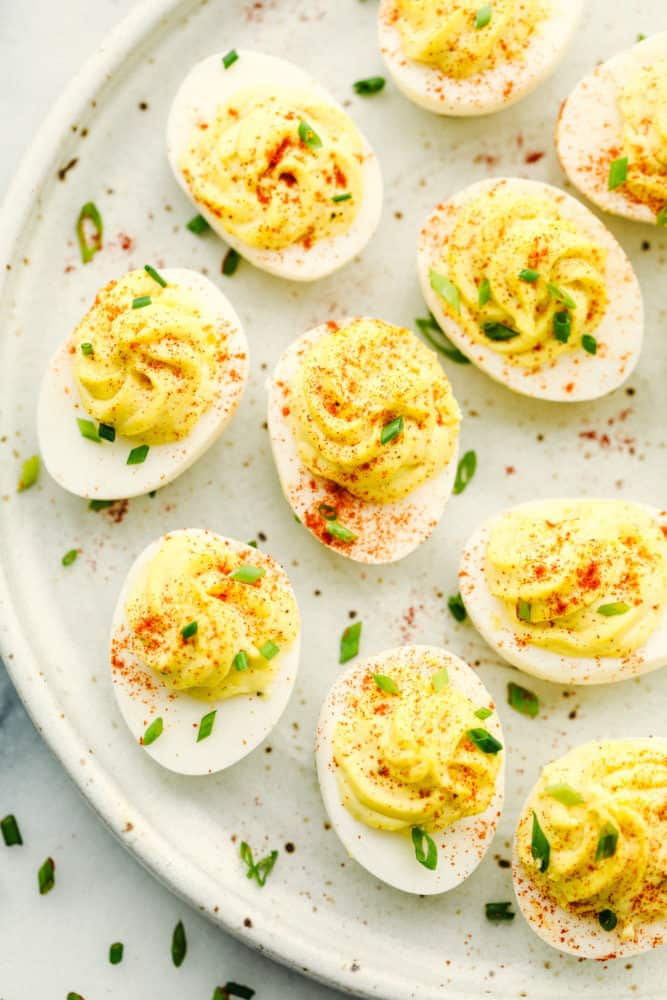Deviled eggs on a plate with paprika sprinkled on top.