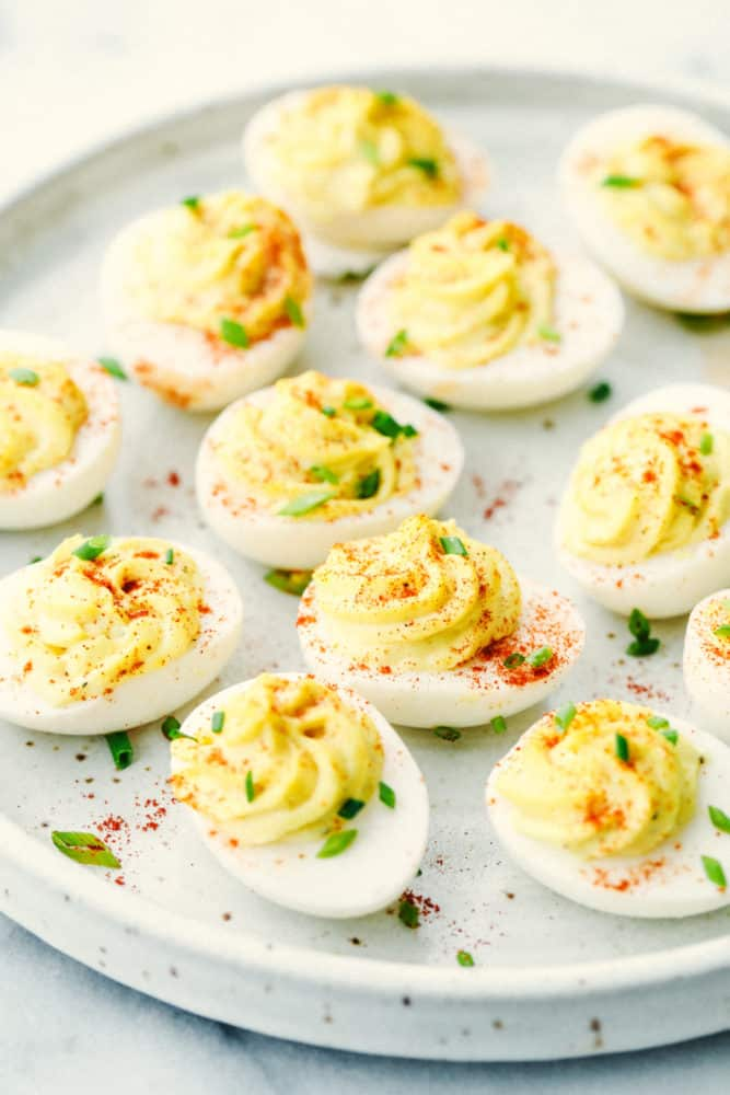 Deviled eggs on a plate with paprika sprinkled over top.