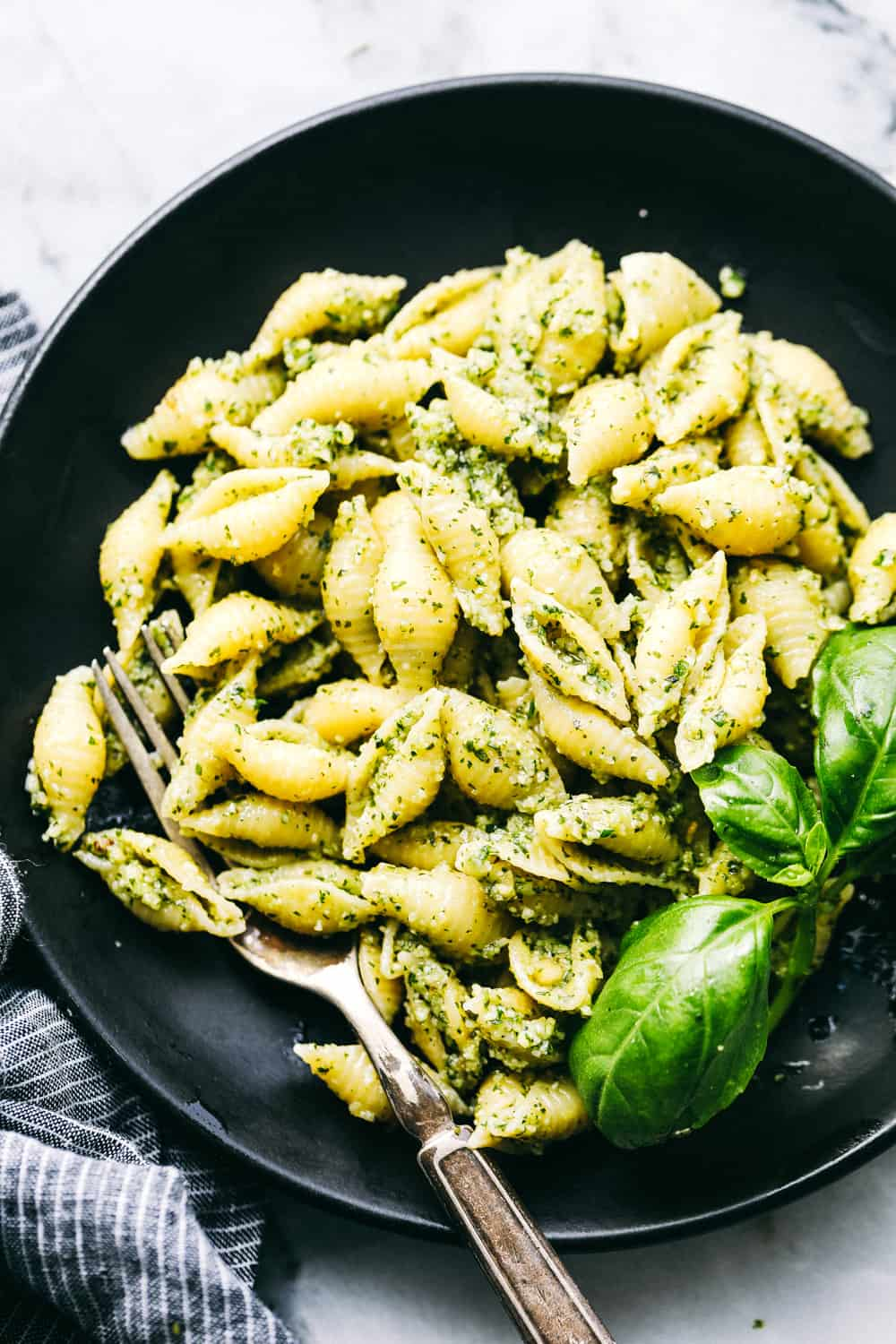 Pesto pasta on a black plate.