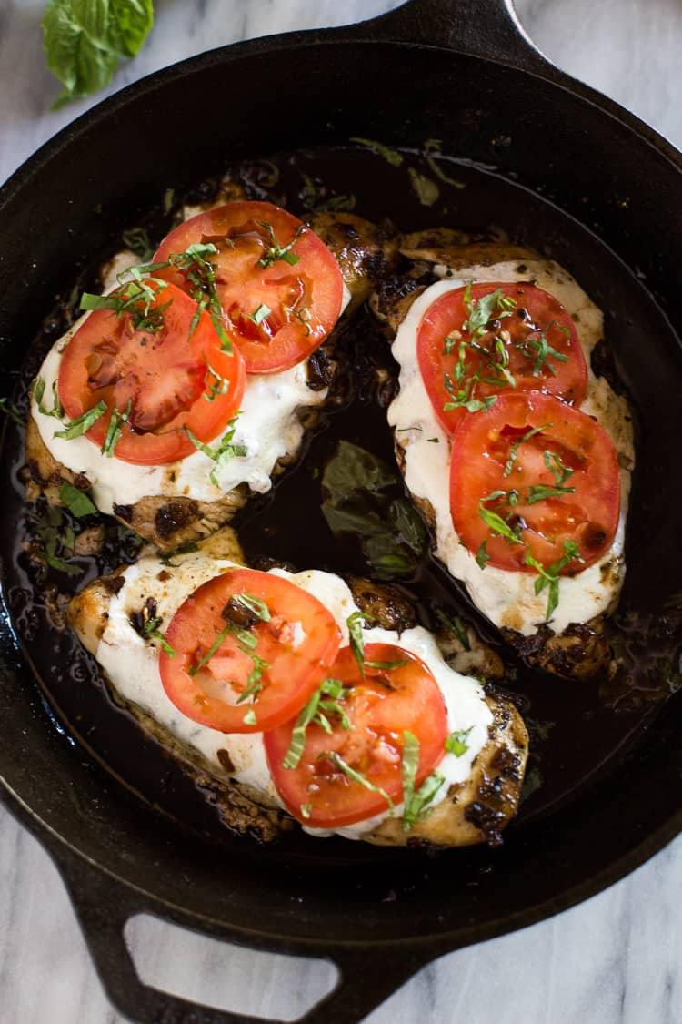 Baked Caprese Chicken in a skillet.
