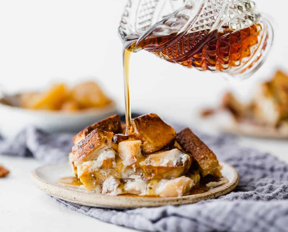 Pouring syrup on french toast casserole on a plate.