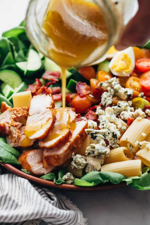Pouring dressing on pasta cobb salad