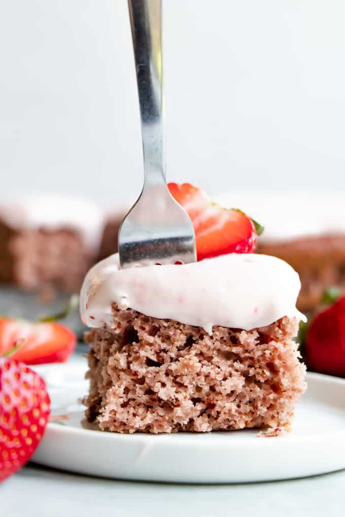 Slice of strawberry cake with a fork in it.