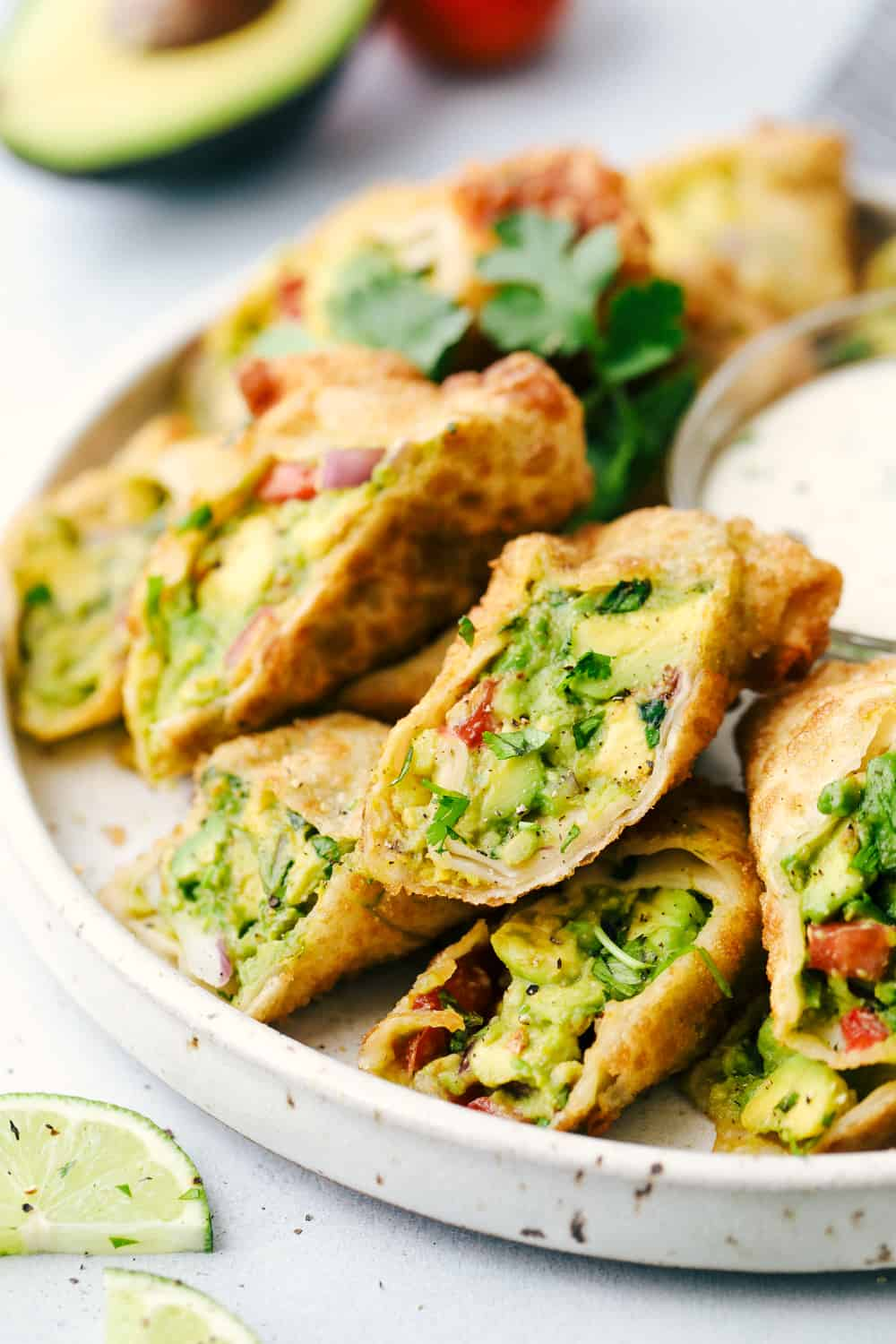 Avocado Egg Rolls in a stack on a plate with dip.