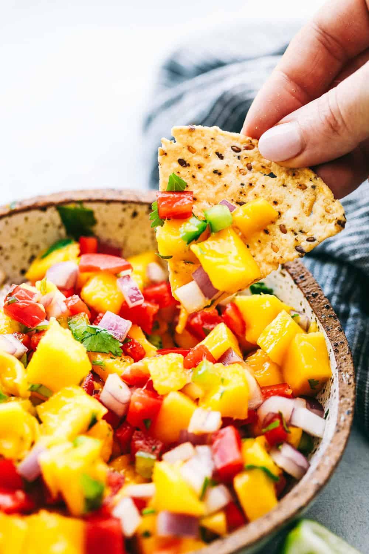 chip scooping mango salsa.