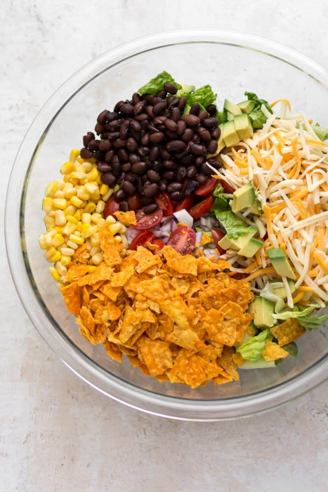 beef taco salad ingredients in a clear bowl.