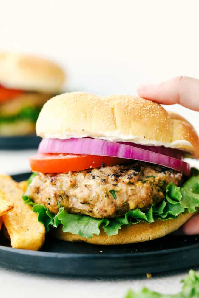 Turkey burger on a black plate with red onion, tomato and lettuce with fries on the side on a black plate.