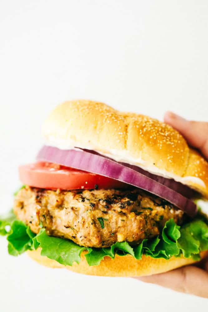 Turkey burger with red onion, tomato and lettuce while being held up by a hand in a white backdrop photo.