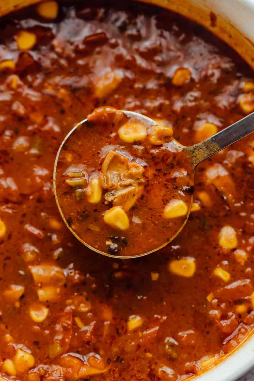 Closeup of a ladleful of chicken tortilla soup