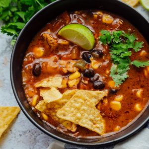 Chicken tortilla soup served in a black bowl with toppings