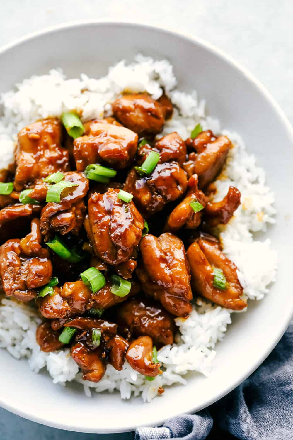 bourbon chicken over white rice and garnished with green onions