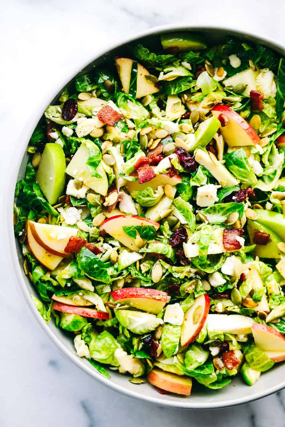 apple bacon Brussels sprouts salad in a bowl.