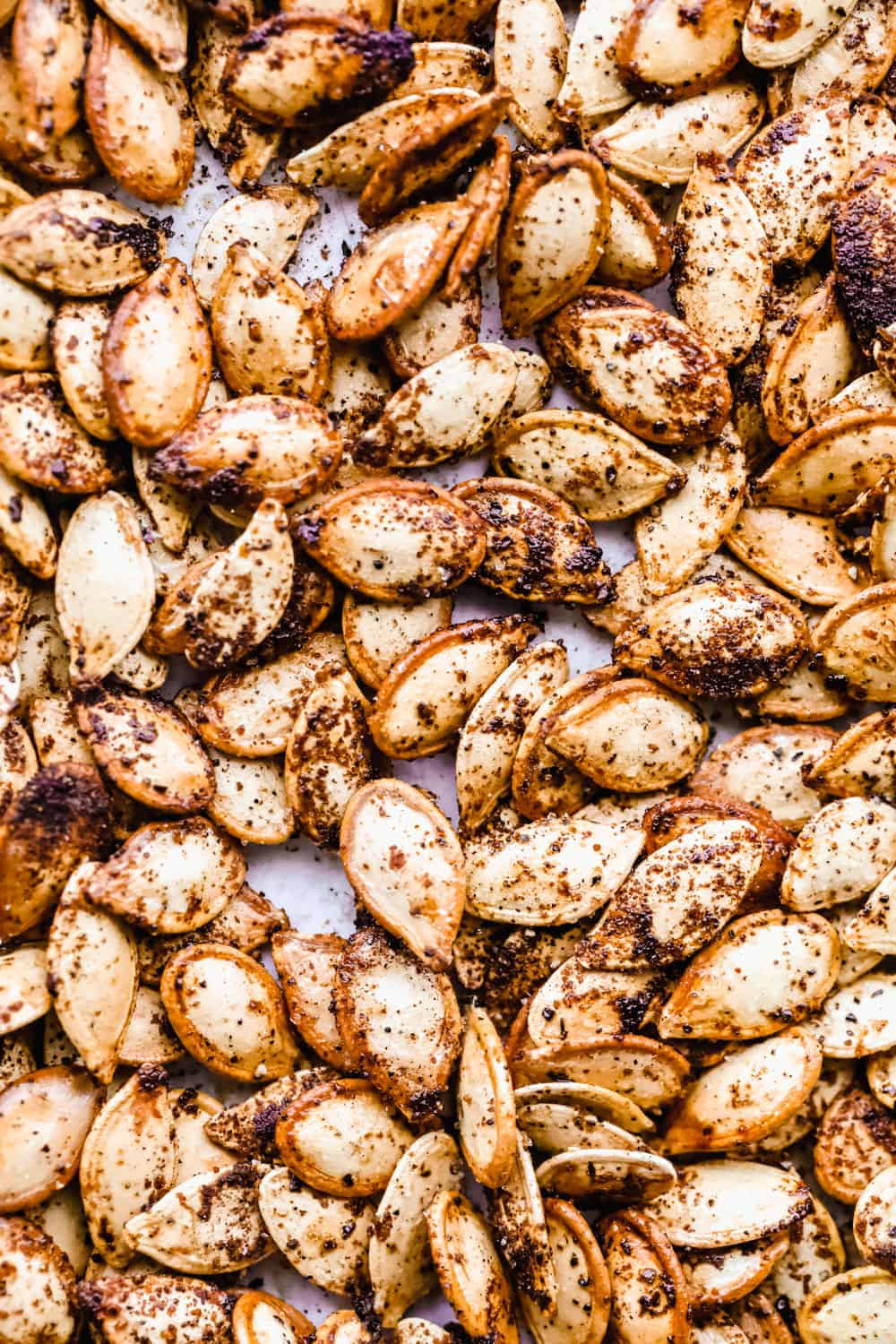 Roasted pumpkin seeds on a baking sheet.