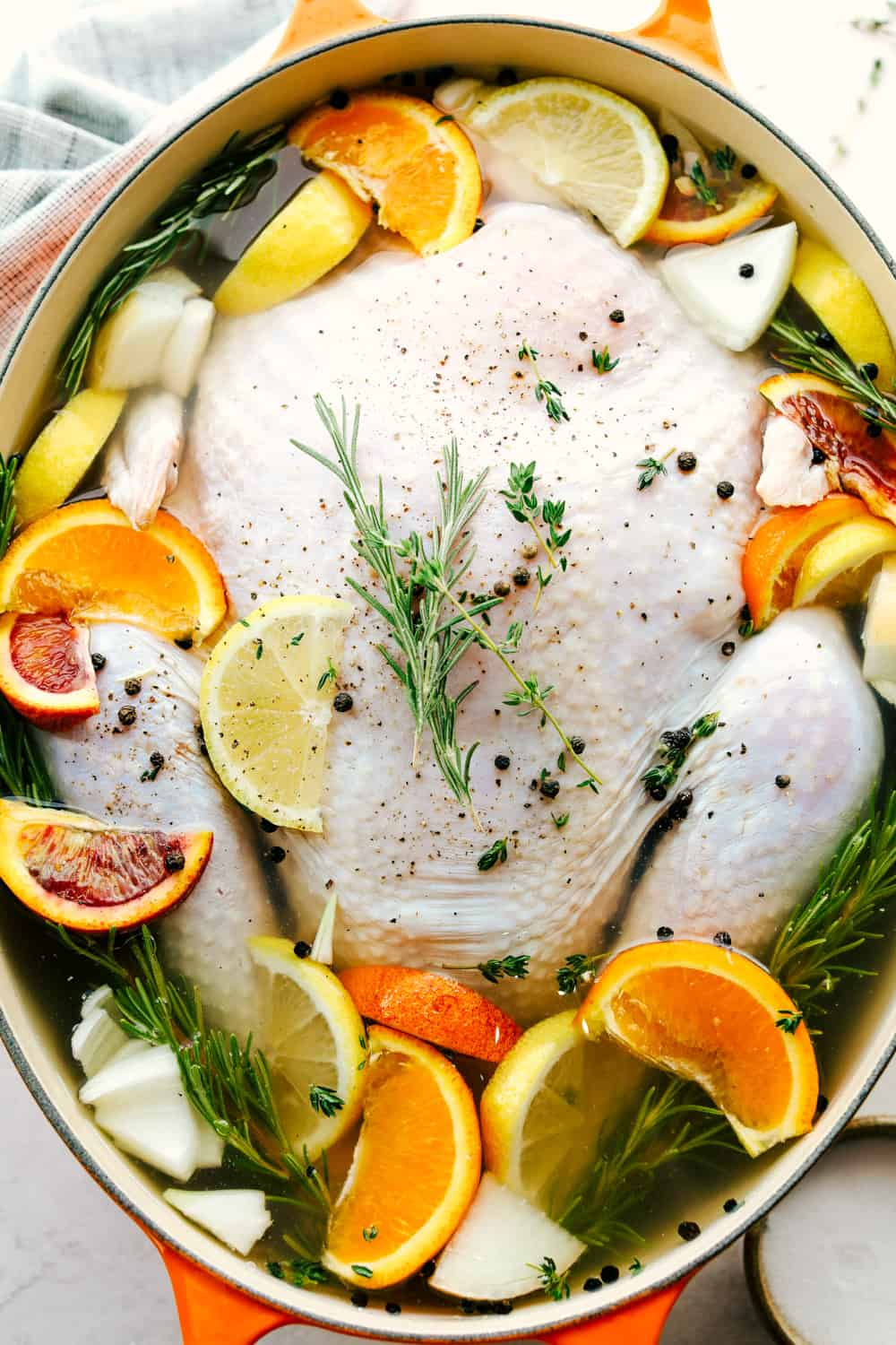Turkey in a pot being submerged by water and other seasonings for a brine.
