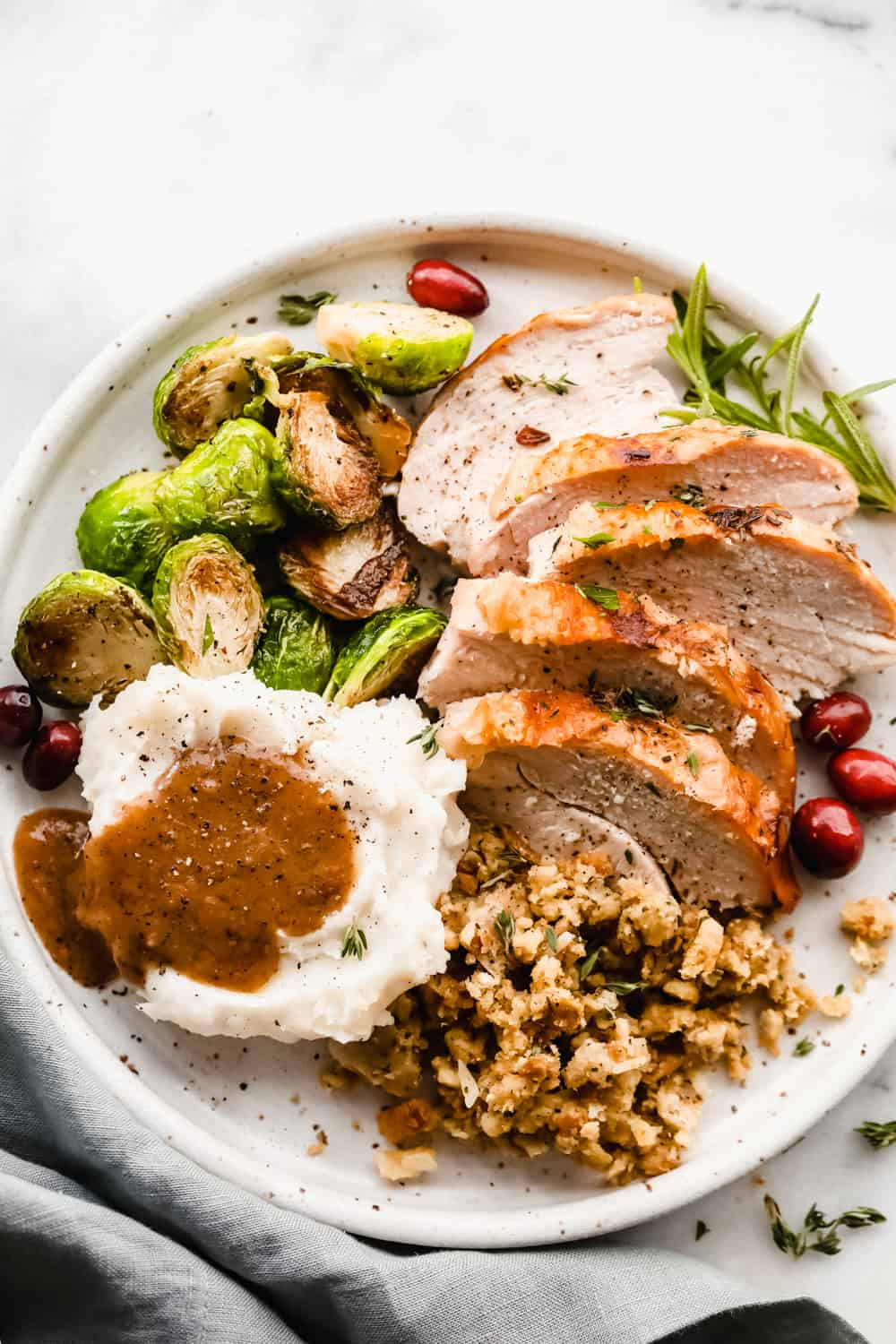 sliced turkey, mashed potatoes with turkey gravy, Brussel sprouts and pilaf all plated together.