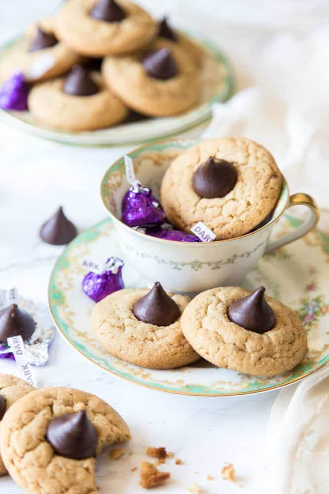 Peanut butter blossom cookies on plates and in tea cup