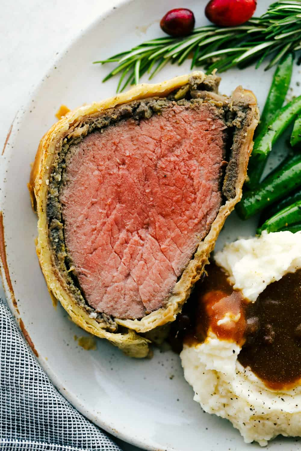 Beef Wellington sliced onto a plate with mashed potatoes and green beans