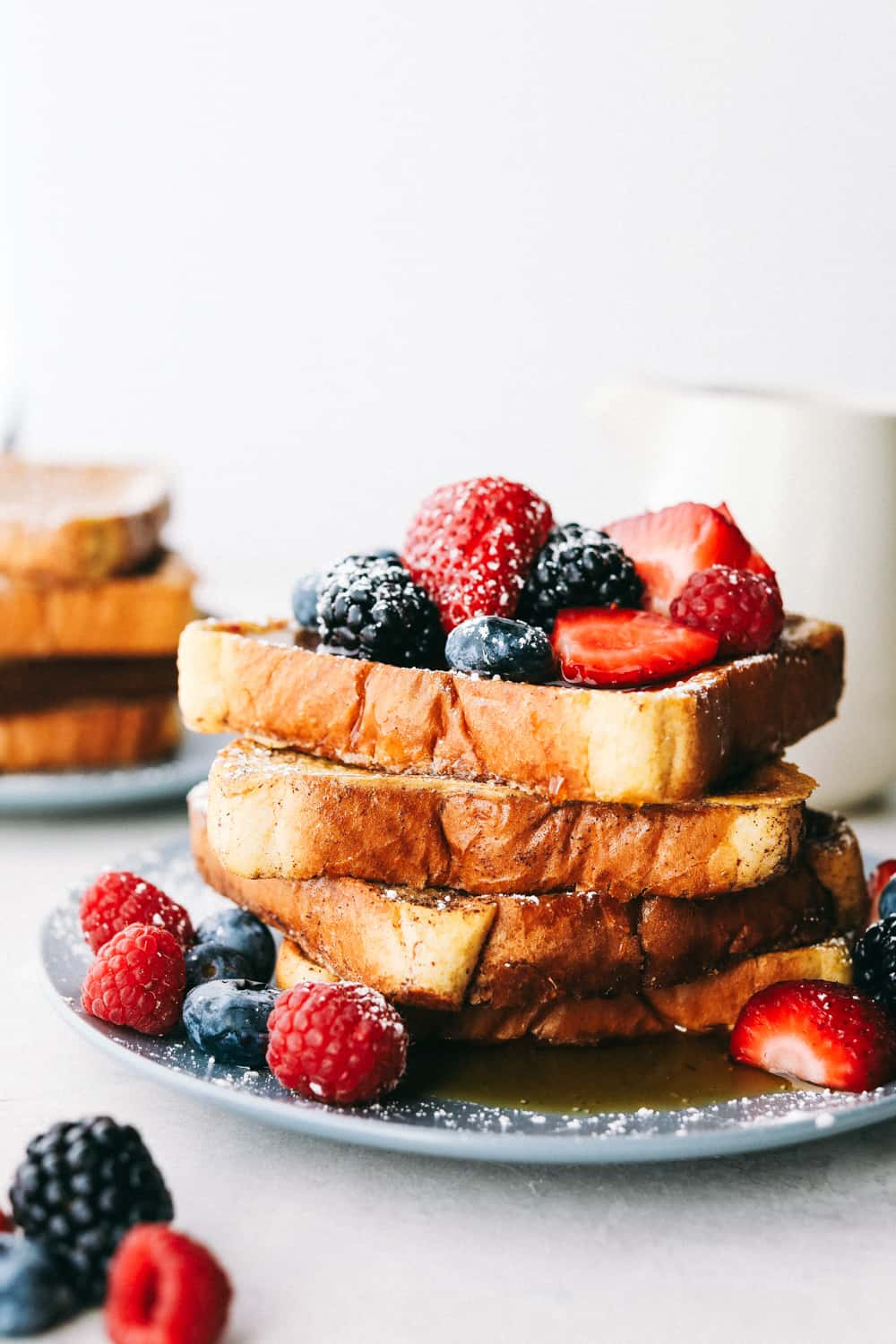 French toast stacked up with berries and powdered sugar on them.