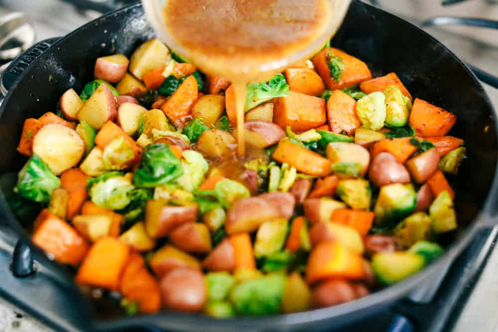 vegetables cooking on the stove top while adding a maple dijon marinate over top of them.