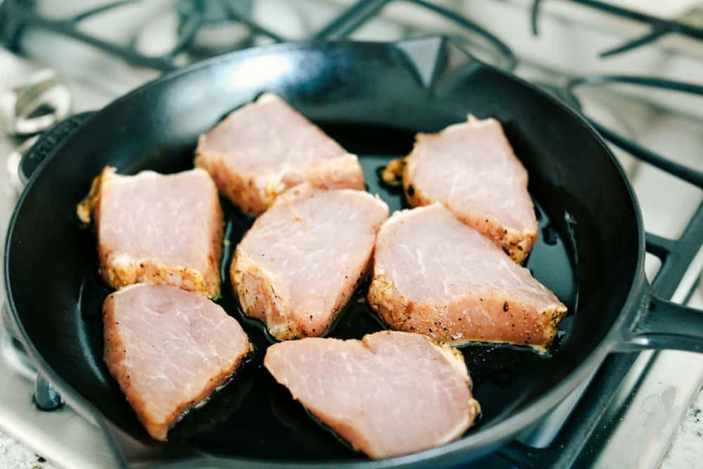 pork chops in a skillet cooking