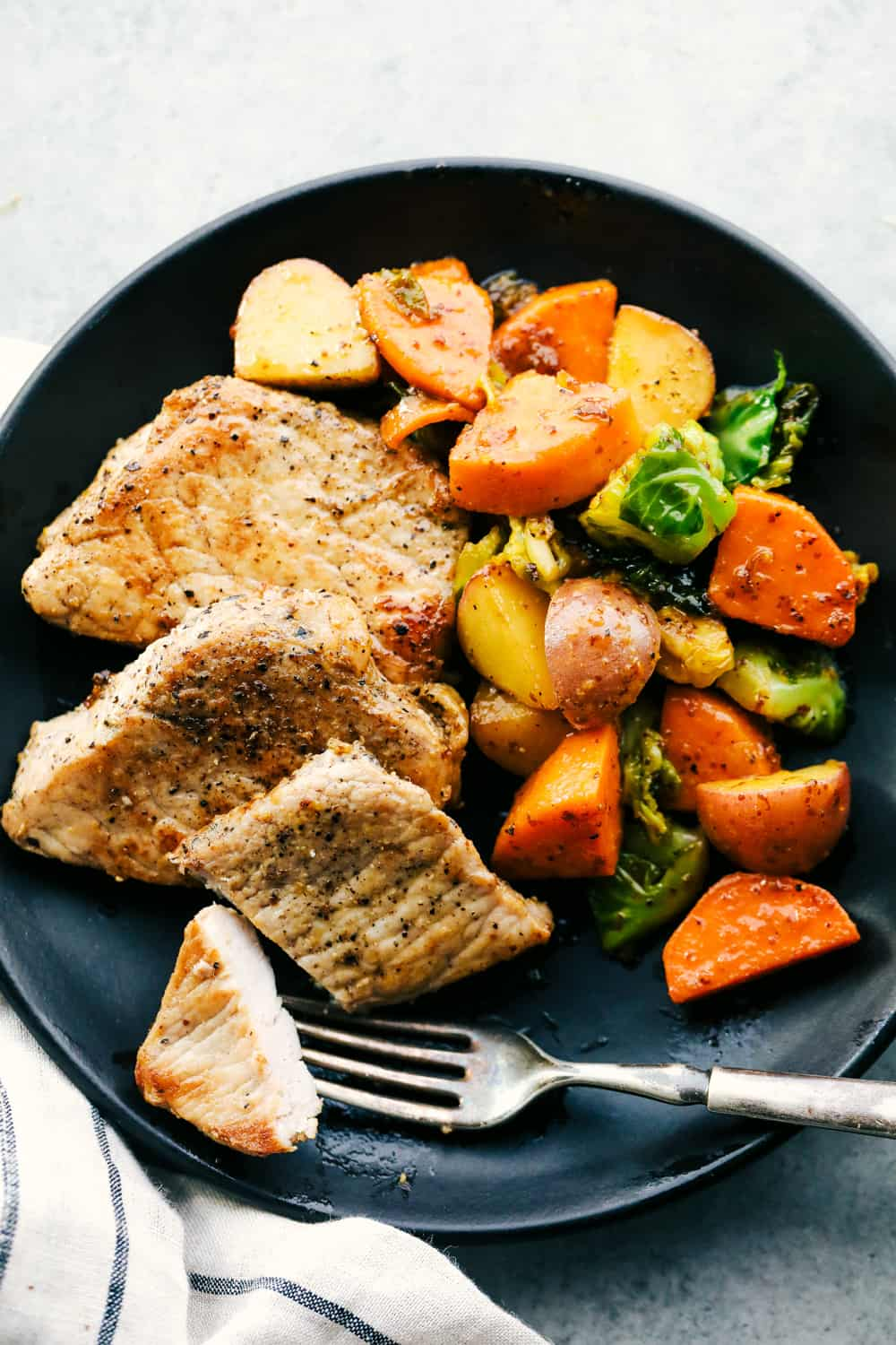 skillet pork chops with maple dijon vegetables on a plate