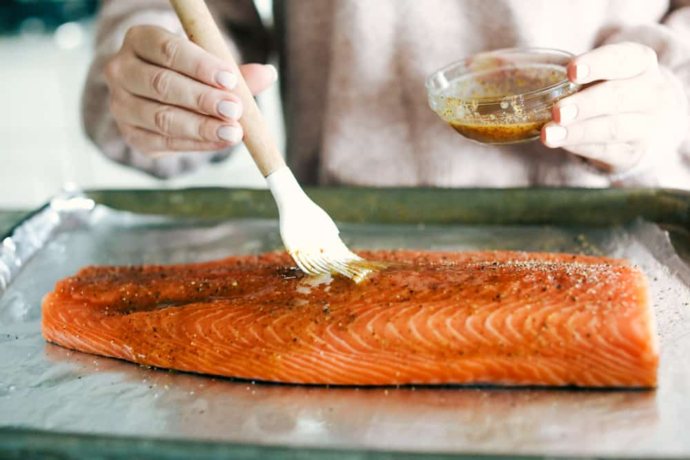 A salmon being basted with the marinated sauce.