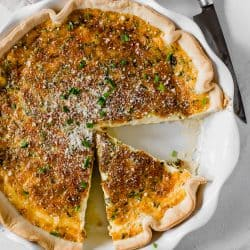 quiche with slices cut out in white pie dish
