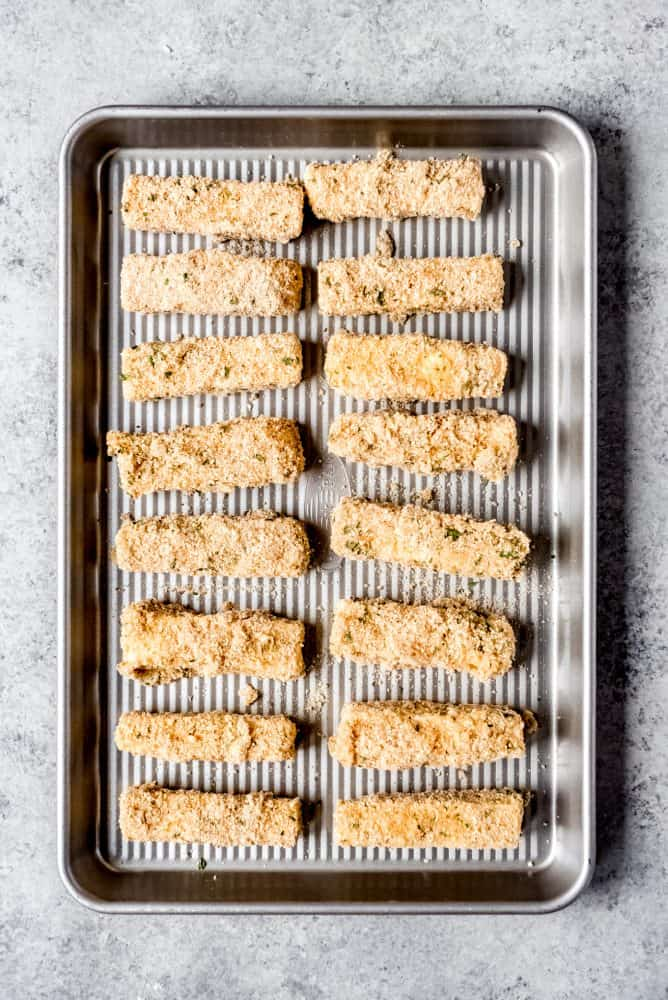 An image of breaded mozzarella sticks on a baking sheet for freezing.