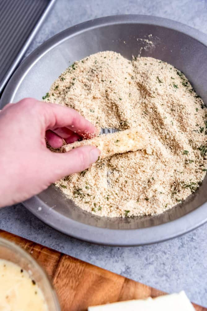 An image of mozzarella cheese being dredged in Italian-seasoned breadcrumbs.