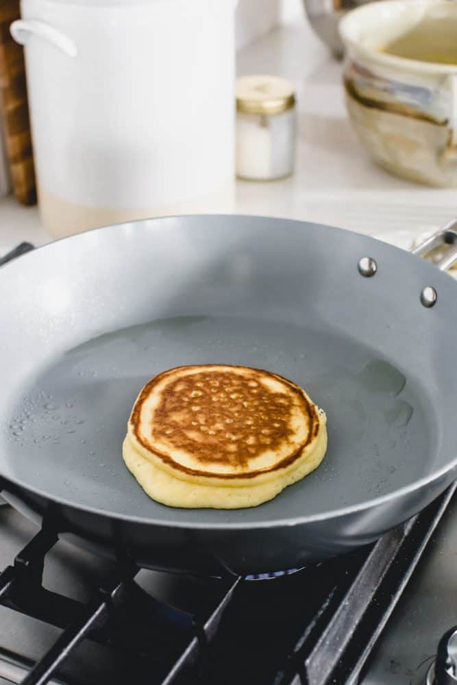 Keto pancake cooking on a skillet over the gas stove top.