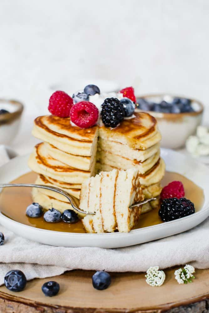 Keto pancakes stacked together with fresh fruit and whipped topping on top.