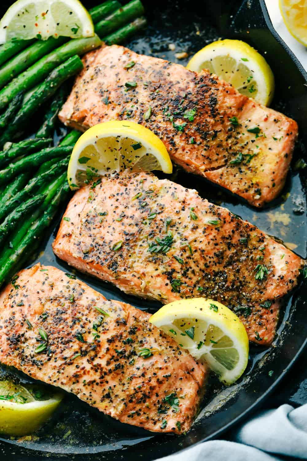 Brown butter lemon salmon being sautéed by lemons and asparagus on the side.