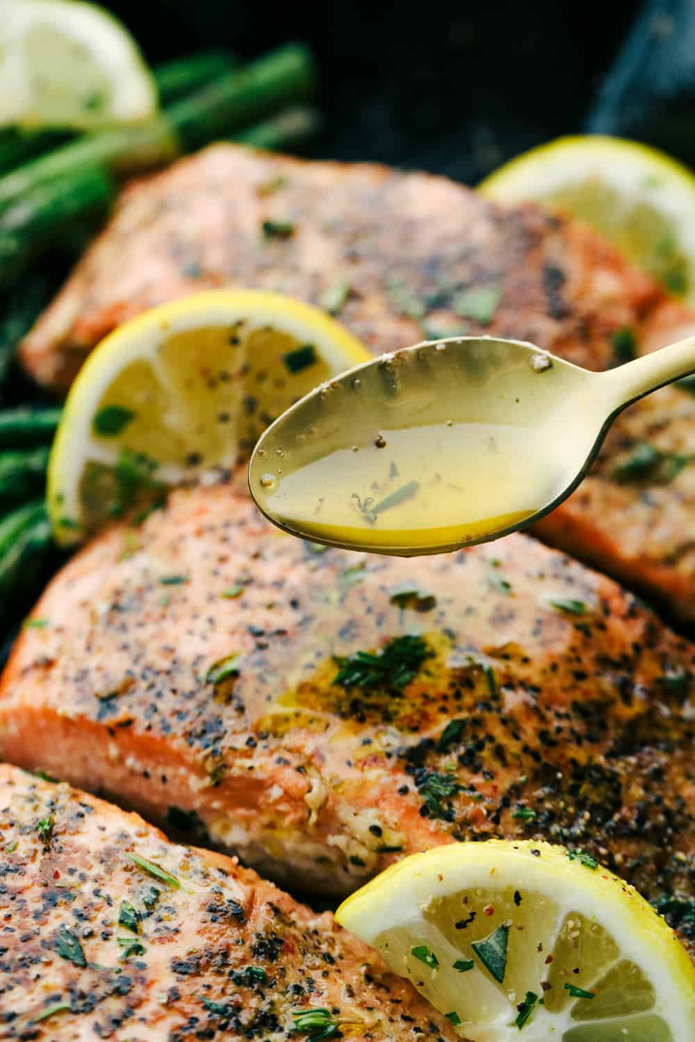 Brown butter lemon salmon with a spoon drizzling brown butter glaze over top of the salmon.