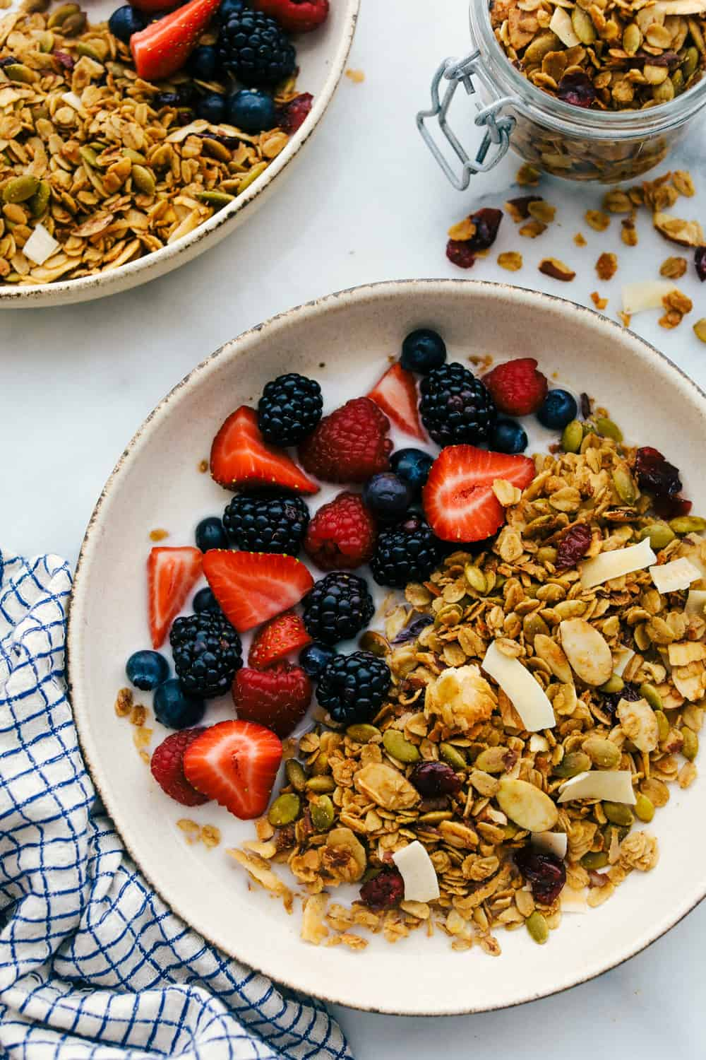 homemade granola in a bowl with fresh fruit and milk.