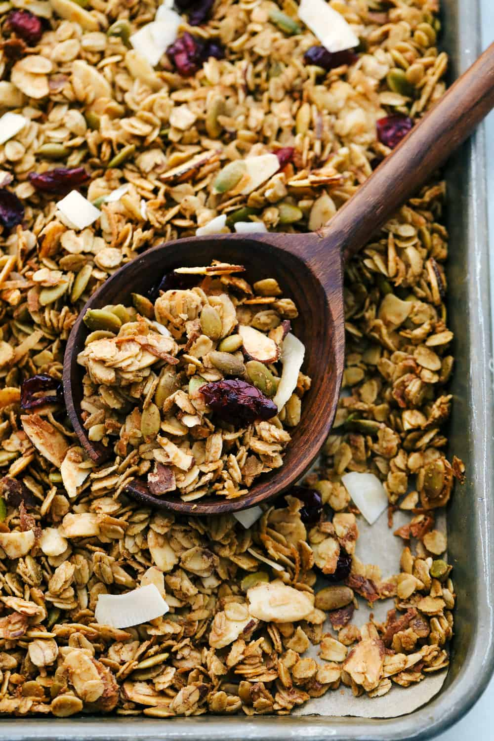 Homemade baked granola on a sheet pan with a large wooden spoon scooping it up.