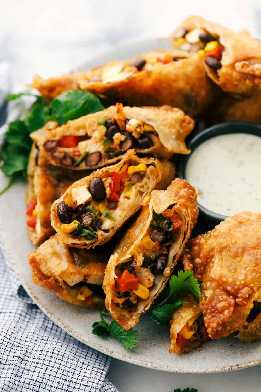 Southwest chicken egg rolls on a plate served with cilantro lime ranch dipping sauce.